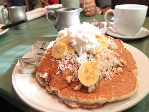 This is a full order or Tropical Pancakes, a stack of seriously fat cakes topped with bananas, coconuts and macadamia nuts. But inside each cake is a layer of molten bananas and coconut. Top this with their homemade coconut syrup and you're set.